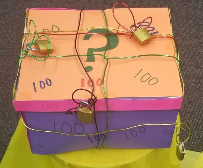 Colorful cardboard box wrapped in wire with multiple locks attached (Classroom Escape Room)