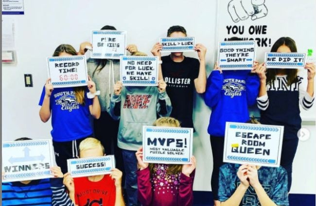 Students celebrating the completion of an escape room by holding up signs